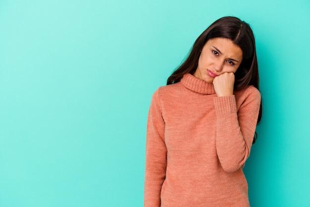 Jovem indiana isolada em um fundo azul que se sente triste e pensativa, olhando para o espaço da cópia.