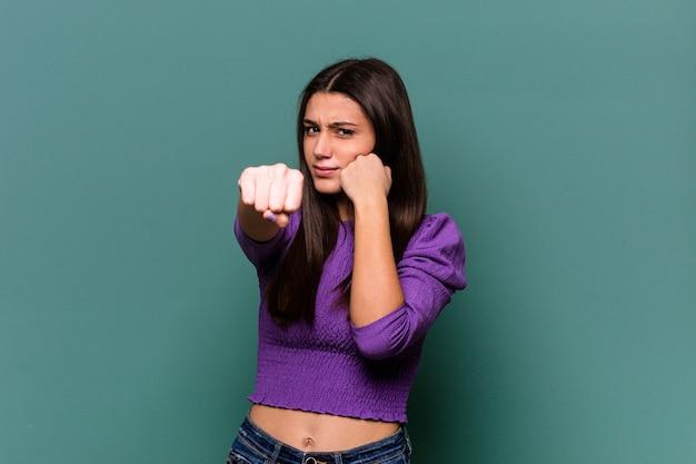 Jovem indiana isolada na parede azul dando um soco, raiva, brigando devido a uma discussão, boxe