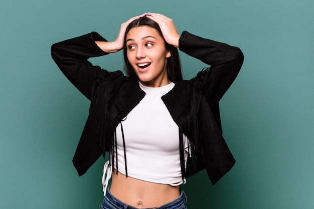 Jovem indiana isolada na parede azul gritando, muito animada, apaixonada, satisfeita com alguma coisa.