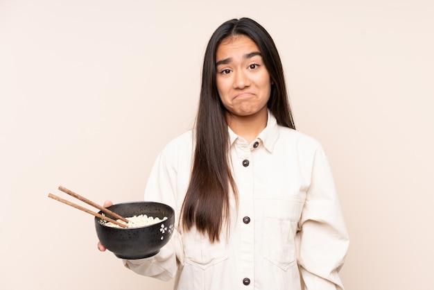 Jovem indiana isolada na parede bege com expressão triste, mantendo uma tigela de macarrão com pauzinhos