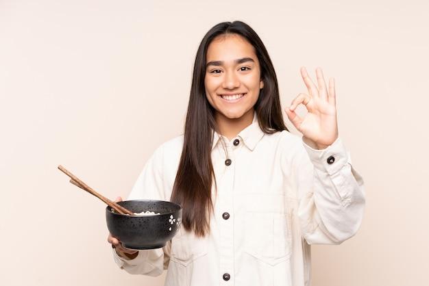 Jovem indiana isolada na parede bege, mostrando sinal de ok com os dedos, mantendo uma tigela de macarrão com pauzinhos
