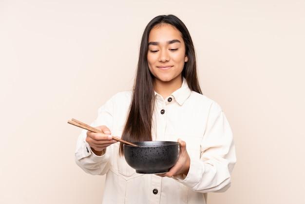 Jovem indiana isolada na parede bege, segurando uma tigela de macarrão com pauzinhos