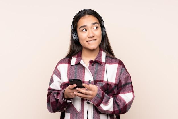 Jovem indiana na música parede bege com um celular e pensando