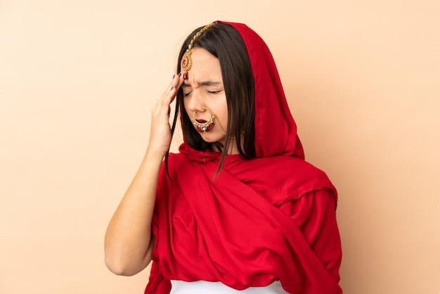 Jovem indiana na parede bege com dor de cabeça