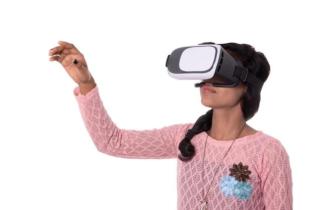 Jovem indiana olhando através do dispositivo vr, fone de ouvido de óculos de realidade virtual 3d, menina com tecnologia de imagem moderna do futuro. Foto Premium