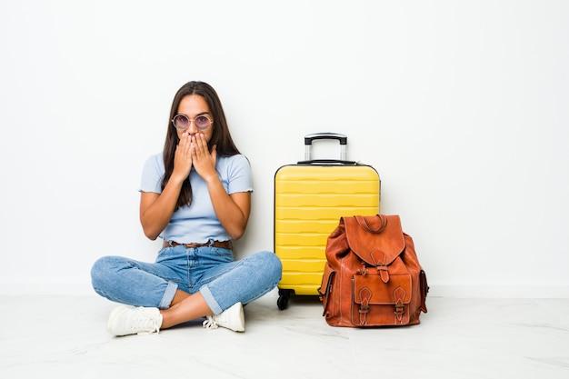 Jovem indiana pronta para ir viajar rindo sobre algo, cobrindo a boca com as mãos