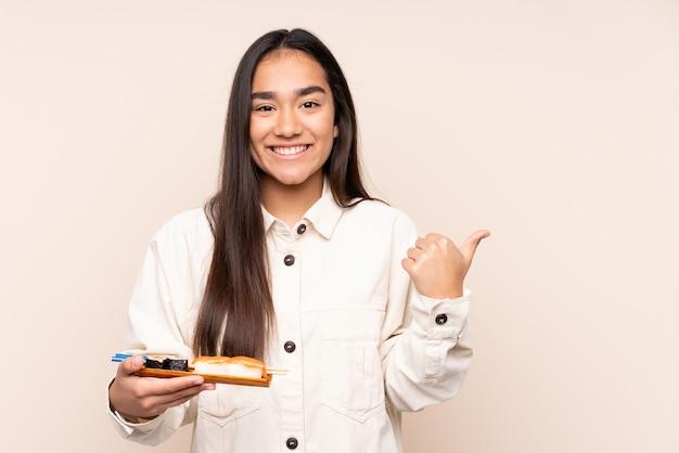 Jovem indiana segurando sushi isolado em bege, apontando para o lado para apresentar um produto