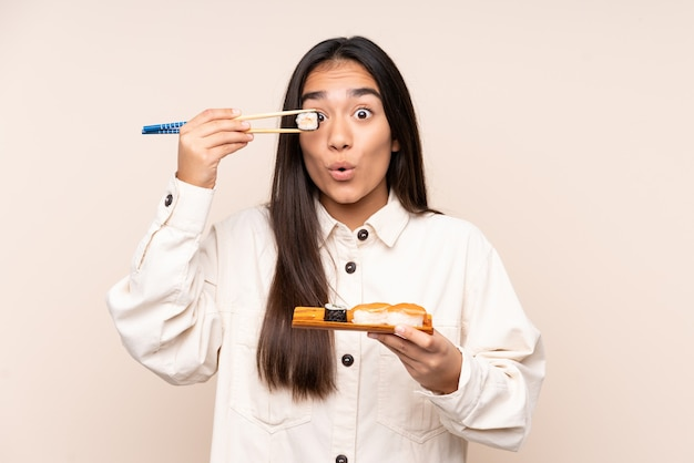 Jovem indiana segurando sushi isolado em bege
