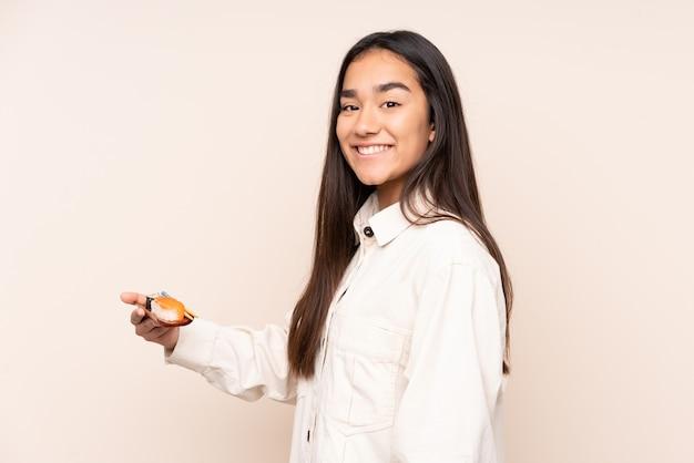 Jovem indiana segurando sushi isolado em um bege e sorrindo muito