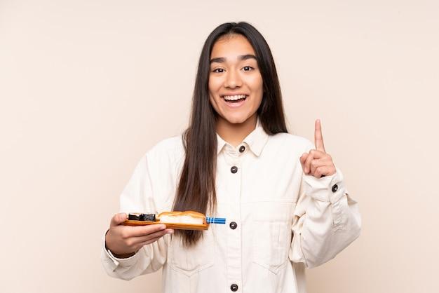 Jovem indiana segurando sushi isolado em um fundo bege apontando uma ótima ideia