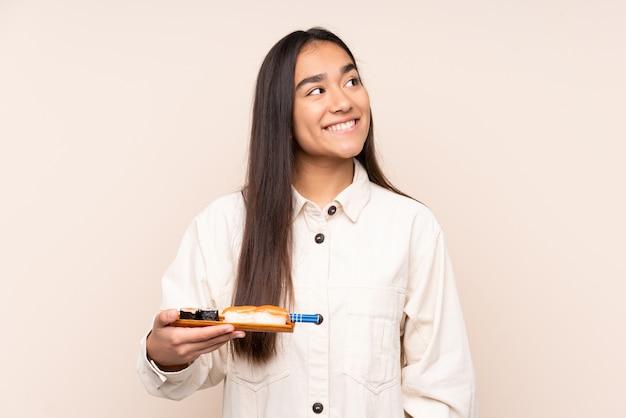 Jovem indiana segurando sushi isolado em um fundo bege, olhando para cima enquanto sorri