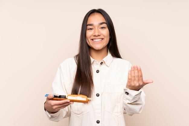 Jovem indiana segurando sushi na parede bege, convidando para vir com a mão