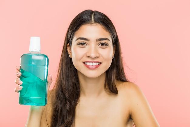 Jovem indiana segurando uma garrafa de colutório feliz, sorridente e alegre