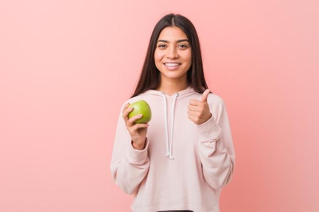 Jovem indiana segurando uma maçã