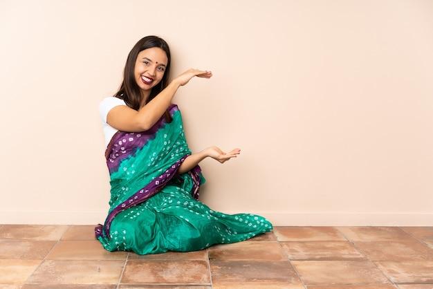 Jovem indiana sentada no chão segurando copyspace para inserir um anúncio