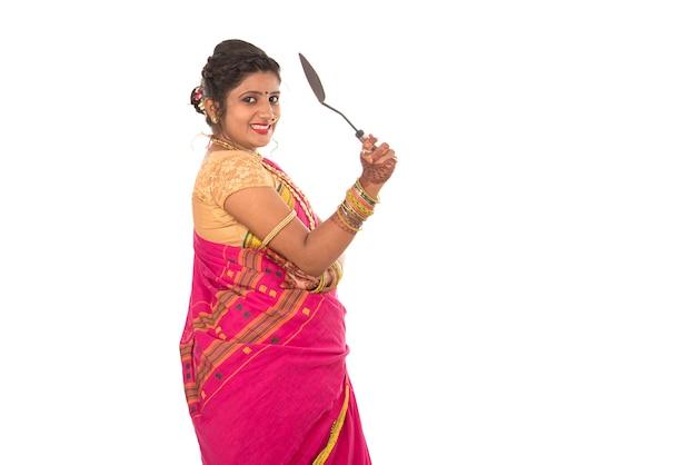 Jovem indiana tradicional segurando um utensílio de cozinha em branco