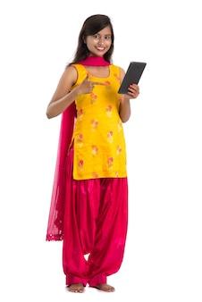 Jovem indiana usando um celular ou smartphone isolado em um branco