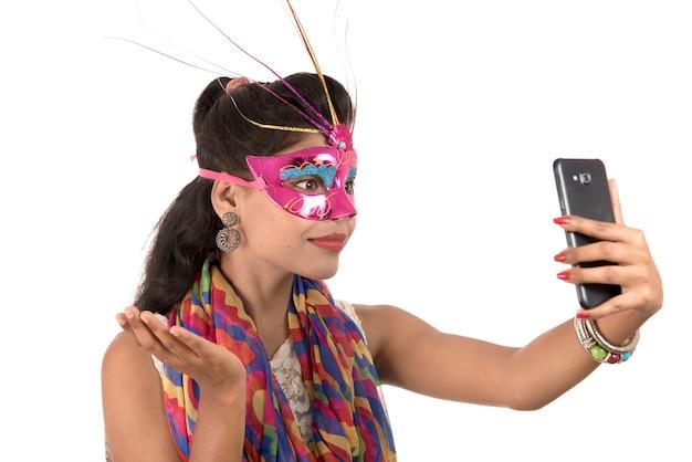 Jovem indiana usando um celular ou smartphone isolado em um fundo branco
