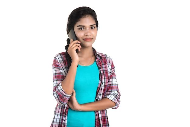 Jovem indiana usando um celular ou smartphone isolado em uma parede branca