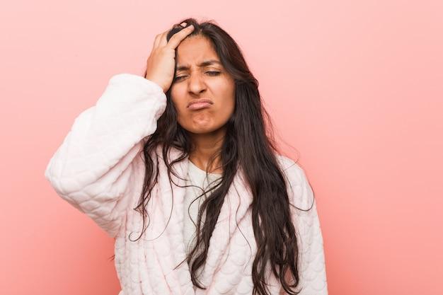 Jovem indiana vestindo pijama cansado e muito sonolento, mantendo a mão na cabeça.
