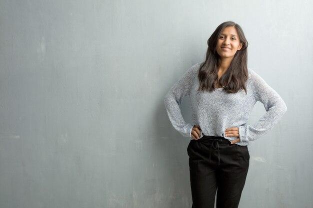 Jovem, indianas, mulher, contra, um, grunge, parede, com, mãos quadrils, ficar, relaxado, e, sorrindo