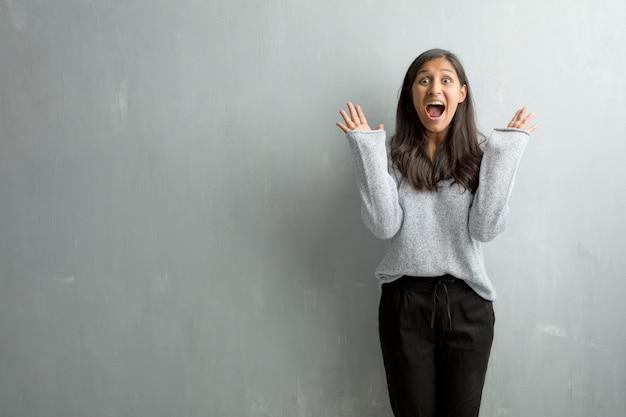 Jovem, indianas, mulher, contra, um, grunge, parede, gritando, feliz, surpreendido, por, um, oferta, ou, um, promo