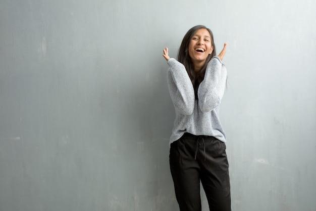 Jovem, indianas, mulher, contra, um, parede grunge, rir, e, tendo divertimento, sendo, relaxado, e, cheerf