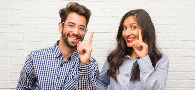 Jovem, indianas, mulher, e, caucasiano, par homem, mostrando, numere um, símbolo, de, contagem