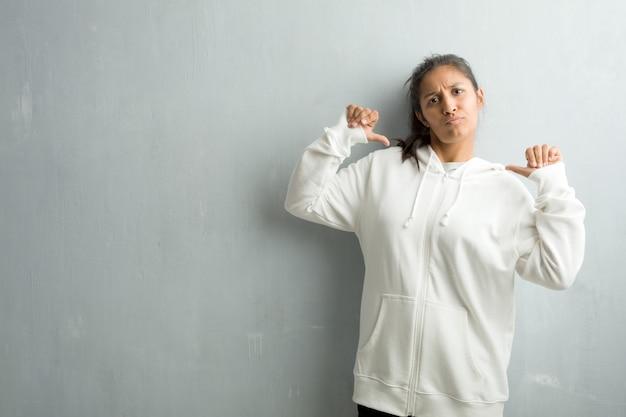 Jovem, indianas, sporty, mulher, contra, ginásio, parede, orgulhoso, confiante, apontar, dedos