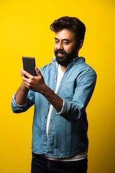 Jovem indiano barbudo usando smartphone, sorrindo ao ligar ou conversar com um amigo, em pé no amarelo