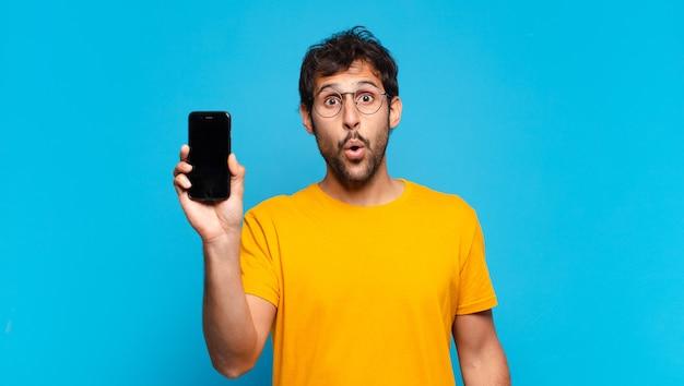 Jovem indiano bonito com expressão de medo e segurando um telefone celular