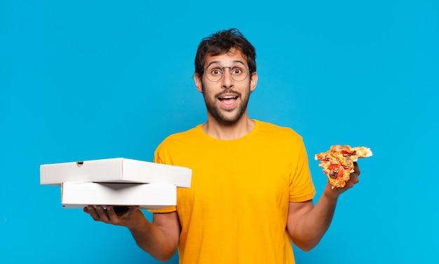 Jovem indiano bonito com expressão de surpresa e segurando pizzas para viagem