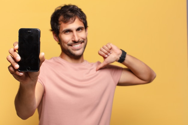 Jovem indiano bonito comemorando e exssão orgulhosa do conceito de smartphone
