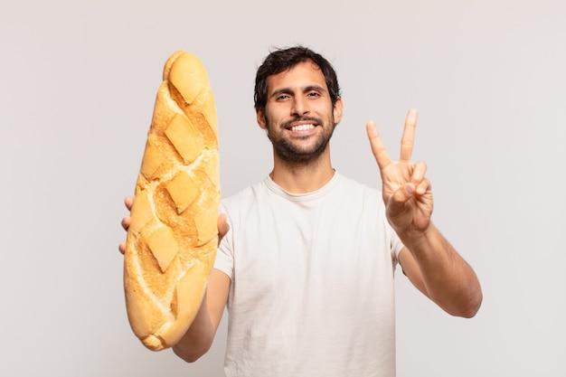 Jovem indiano bonito comemorando uma vitória bem-sucedida e segurando um pão