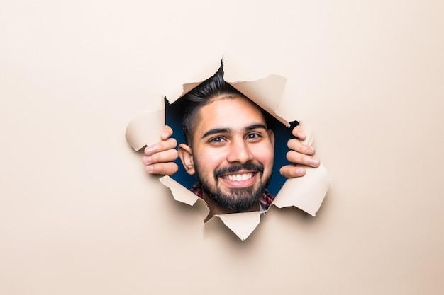 Jovem indiano bonito e barbudo sorrindo olhando de um buraco de papel bege