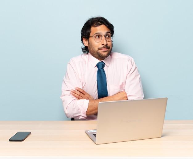 Jovem indiano bonito encolhendo os ombros, sentindo-se confuso e incerto, duvidando com os braços cruzados e olhar perplexo. conceito de negócios e frelancer