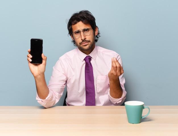 Jovem indiano bonito fazendo capice ou gesto de dinheiro, dizendo para você pagar suas dívidas !. conceito de negócios