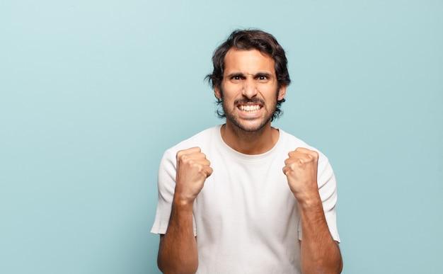 Jovem indiano bonito gritando agressivamente com olhar irritado, frustrado e irritado