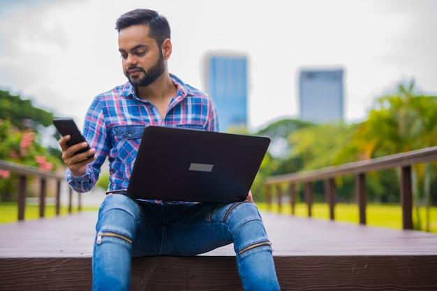 Jovem indiano bonito no parque usando um laptop e um telefone celular