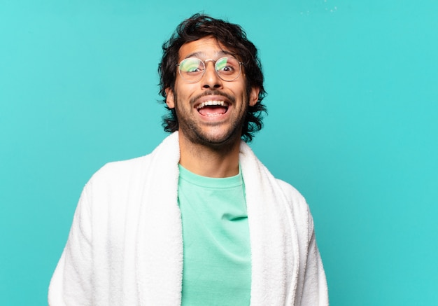 Jovem indiano bonito parecendo feliz e agradavelmente surpreso, animado com uma expressão de fascínio e choque e vestindo um roupão de banho