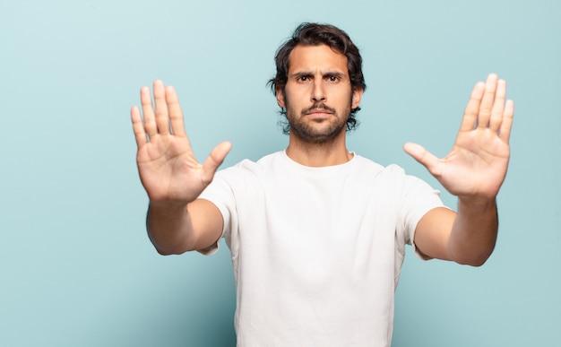 Jovem indiano bonito parecendo sério, infeliz, irritado e descontente, proibindo a entrada ou dizendo para com as duas mãos abertas