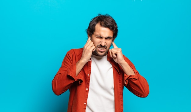Jovem indiano bonito parecendo zangado, estressado e irritado, cobrindo os ouvidos com um barulho, som ou música alta ensurdecedores