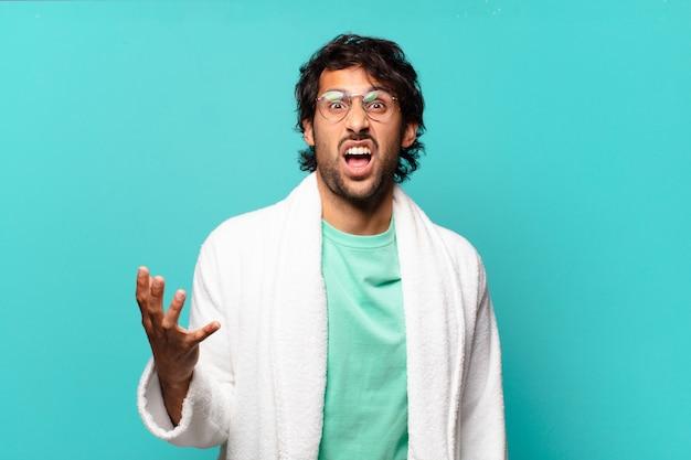 Jovem indiano bonito parecendo zangado, irritado e frustrado gritando wtf ou o que há de errado com você e vestindo roupão de banho