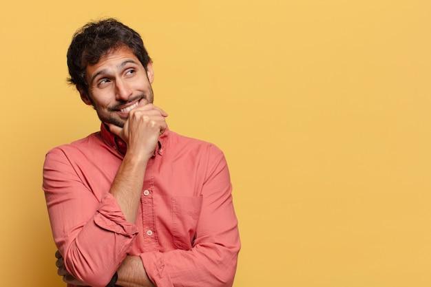Jovem indiano bonito pensando ou duvidando da expressão