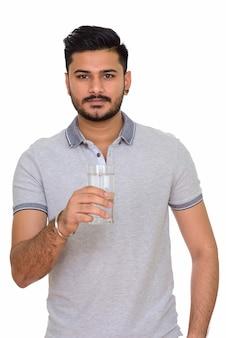 Jovem indiano bonito segurando um copo d'água