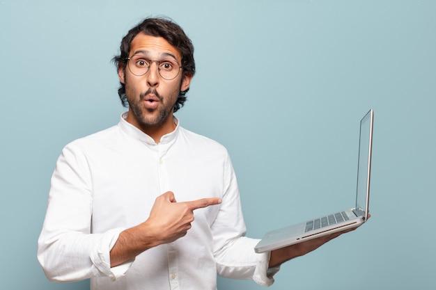 Jovem indiano bonito segurando um laptop