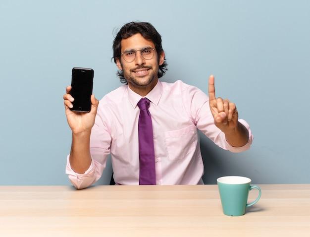 Jovem indiano bonito sorrindo e parecendo amigável, mostrando o número um ou primeiro com a mão para a frente, em contagem regressiva. conceito de negócios