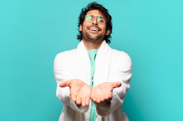 Jovem indiano bonito sorrindo feliz com um olhar amigável, confiante e positivo, oferecendo e mostrando um objeto ou conceito e vestindo roupão de banho