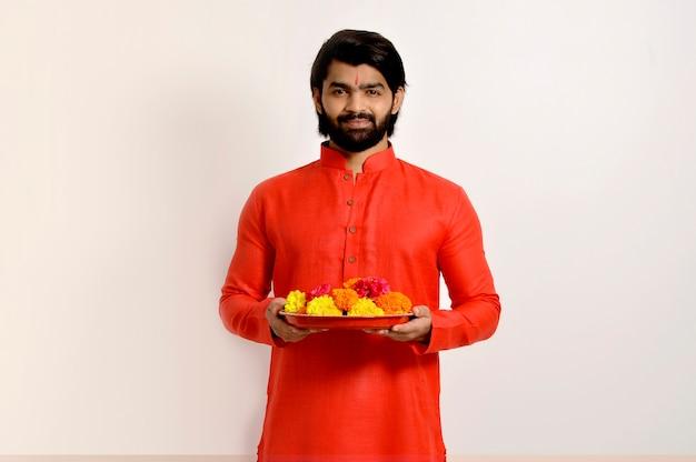 Jovem indiano bonito usando kurta, exibição de fonte, segurando calêndula flor thali