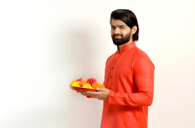 Jovem indiano bonito usando kurta, vista lateral, segurando flower thali